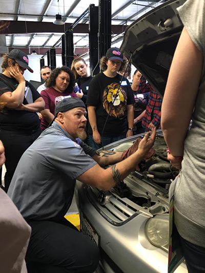 Kniesel's staff demonstrating how to check under the hood.