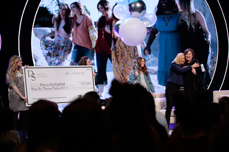 Pastor Debbie Lindell and the Designed Sisterhood team presenting Nancy Alcorn with $35,000 in honor of Mercy Multiplied's 35th Anniversary