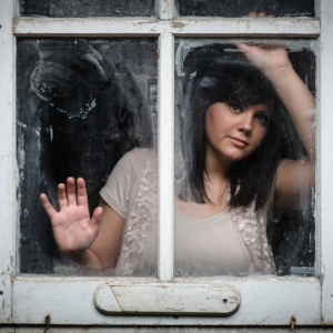 Young woman pressed against a window